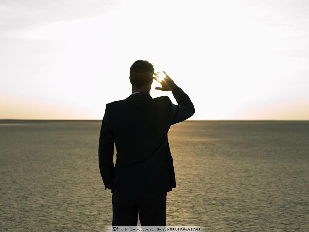 用手遮挡刺眼阳光男人背影图片